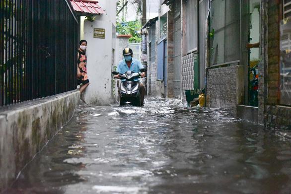 TP.HCM mưa trắng trời, nhân viên trực chốt đẩy xe dân qua chỗ ngập - Ảnh 6.