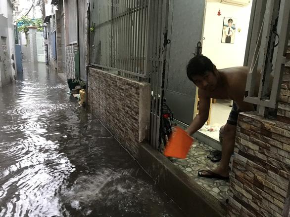 TP.HCM mưa trắng trời, nhân viên trực chốt đẩy xe dân qua chỗ ngập - Ảnh 7.