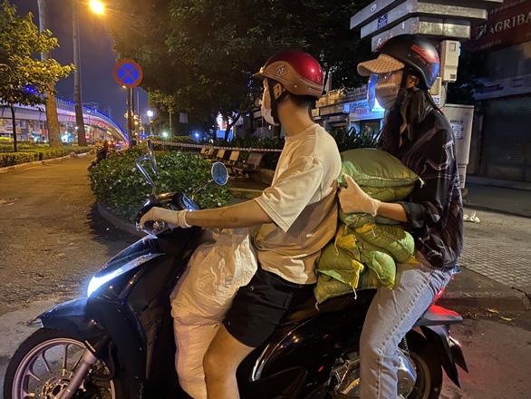 Hoa hậu Trần Tiểu Vy đi xe máy trao 3 tấn gạo cho người nghèo, người vô gia cư tại TP.HCM - Ảnh 1.