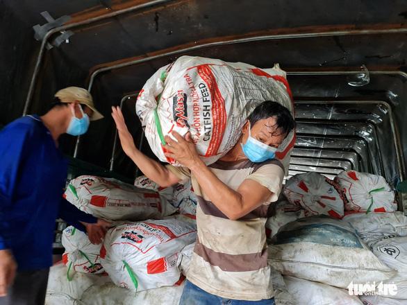 Dầm mưa bốc 22 tấn bắp, chanh bán giá vốn giúp nông dân miền Tây - Ảnh 1.