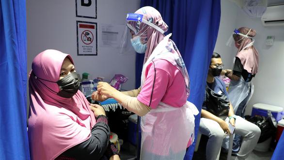Malaysia rà từng ngõ, gõ từng nhà tiêm vắc xin - Ảnh 1.