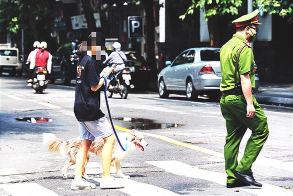 Dắt chó đi vệ sinh ngày đầu Hà Nội giãn cách, cô gái bị phạt 2 triệu - Ảnh 1.