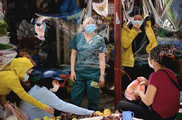 Chợ Hà Nội bắt đầu quây tấm chắn ni lông để bán hàng - Ảnh 1.
