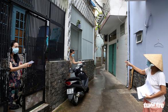 TP.HCM gõ cửa từng nhà phát phiếu đi chợ cho người dân - Ảnh 1.