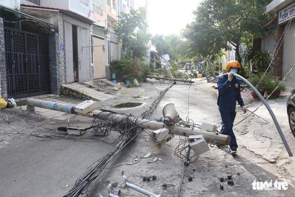 Xe container kéo ngã 9 trụ điện trên đường tại quận 7 trong đêm - Ảnh 1.