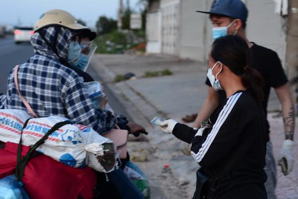 Người phụ nữ mang dép lê đi phát tiền giúp người về quê - Ảnh 2.