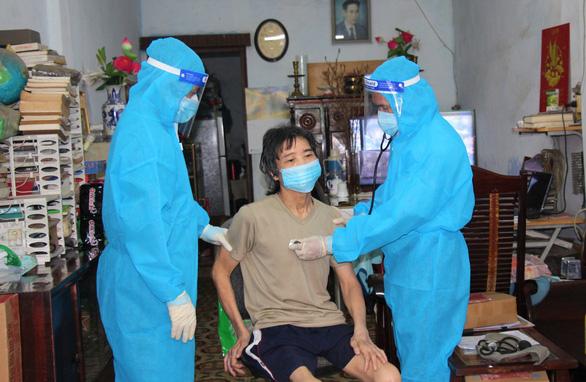 Nhân viên y tế đi xe máy đến tận nhà dân tiêm vắc xin COVID-19 - Ảnh 1.