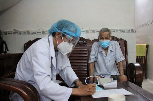 Nhân viên y tế đi xe máy đến tận nhà dân tiêm vắc xin COVID-19 - Ảnh 4.