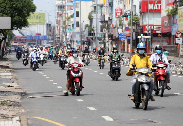 Gần trưa, đường phố TP.HCM vẫn đông người đi lại - Ảnh 1.