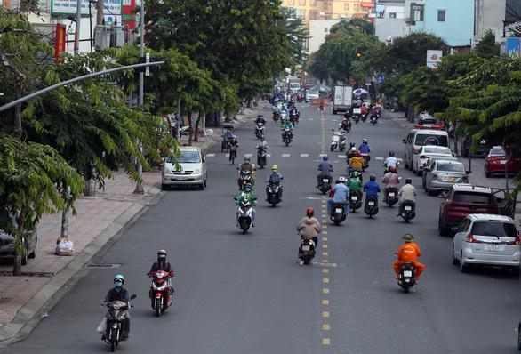Gần trưa, đường phố TP.HCM vẫn đông người đi lại - Ảnh 2.