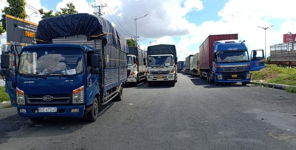 Hàng chục xe chở hàng thiết yếu bị kẹt tại chốt do quy định phải xuống hàng sang xe - Ảnh 1.