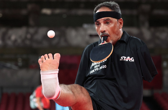 VĐV bóng bàn cụt tay gây ấn tượng ở Paralympic nhờ thi đấu bằng... miệng - Ảnh 2.