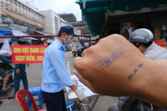 Đóng dấu đã khai báo y tế lên tay người dân đi chợ - Ảnh 1.