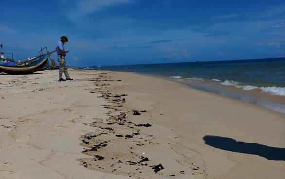 Vết dầu loang dài 5km xuất hiện dọc bờ biển Quảng Bình - Ảnh 1.