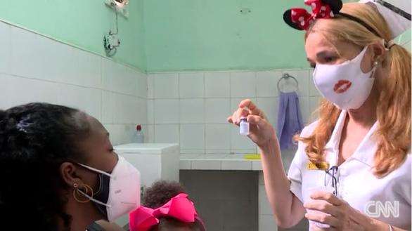 Y bác sĩ Cuba đeo băng đô chuột Mickey khi chích ngừa cho trẻ - Ảnh 1.