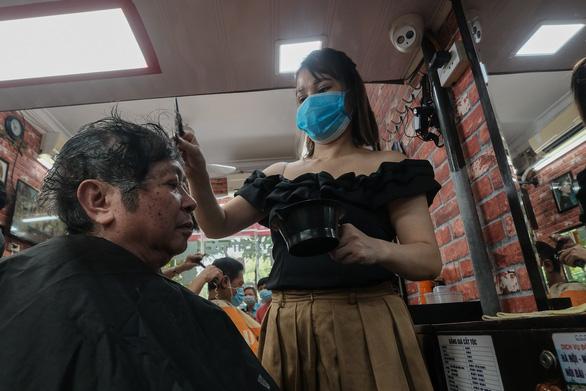 Tiệm cắt tóc vỉa hè, salon tóc đông kín khách ngày đầu mở lại - Ảnh 3.