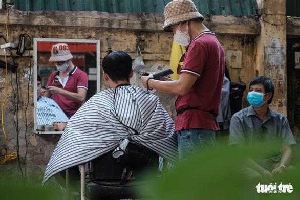 Tiệm cắt tóc vỉa hè, salon tóc đông kín khách ngày đầu mở lại - Ảnh 6.