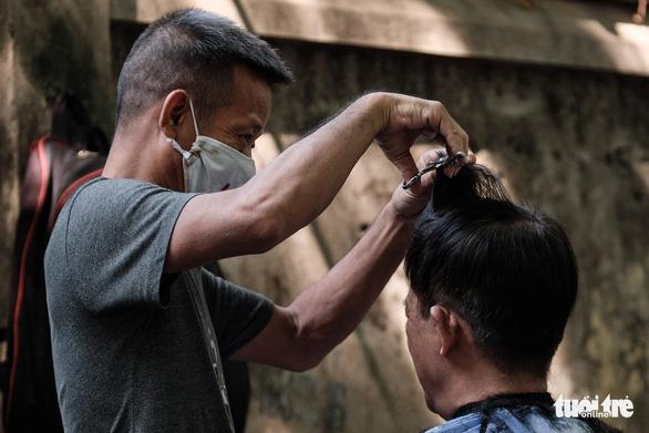 Tiệm cắt tóc vỉa hè, salon tóc đông kín khách ngày đầu mở lại - Ảnh 1.