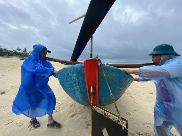Ngư dân Quảng Nam hối hả đưa ghe thuyền lên bờ - Ảnh 1.
