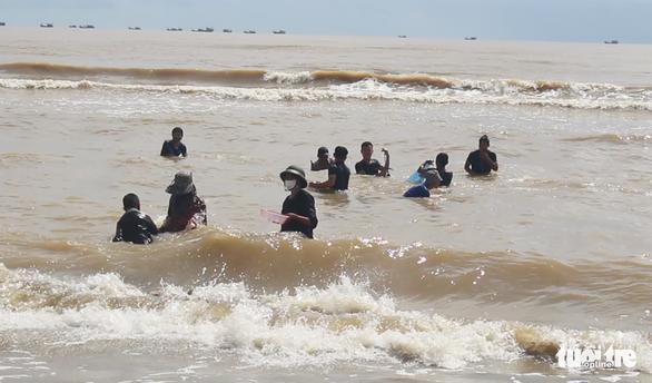 Cả trăm người đi vớt 'lộc biển' dạt vào bờ sau mưa bão - Ảnh 1.