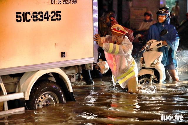 CSGT xuống đường giúp dân đi lại khi ngập nước - ảnh 1