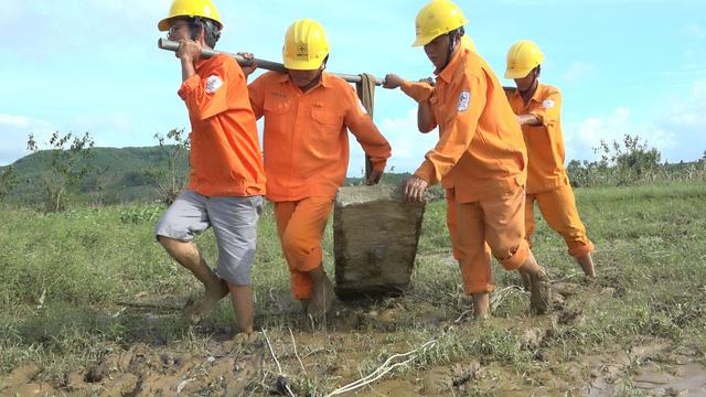 Điện lực Quảng Ngãi vừa sửa điện, vừa cứu trợ dân vùng lũ - Ảnh 1.