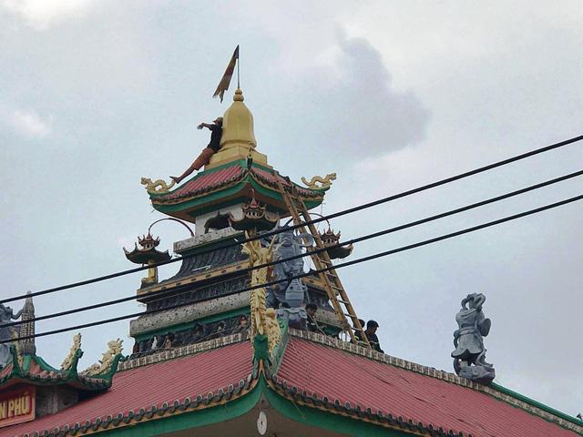 Một thanh niên nghi 'ngáo đá' quậy trên nóc chùa gần 10 giờ - Ảnh 1.