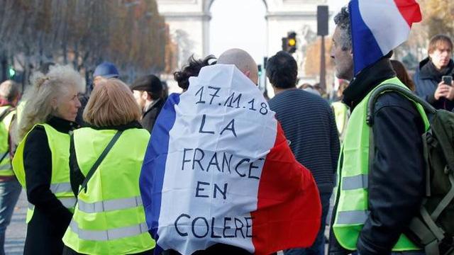 """Người biểu tình với dòng chữ ghi trên lá cờ Pháp """"Nước Pháp nổi giận"""" - (Ảnh qua AFP)"""