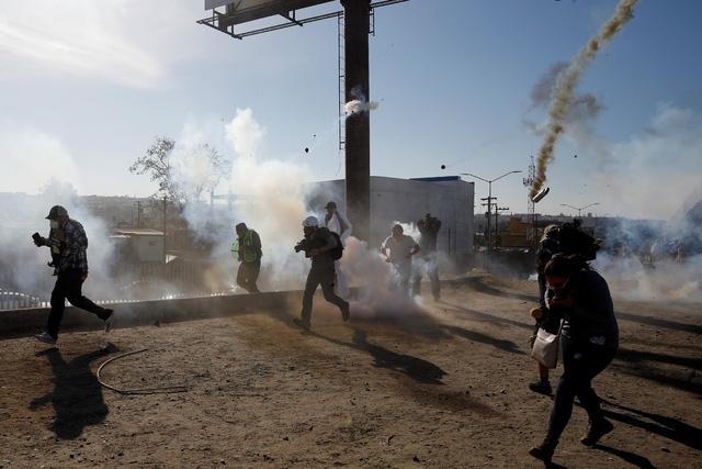 Mỹ bắn hơi cay đuổi người di cư trèo tường vượt biên  - Ảnh 1.