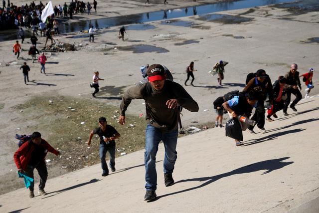 Mỹ bắn hơi cay đuổi người di cư trèo tường vượt biên  - Ảnh 3.