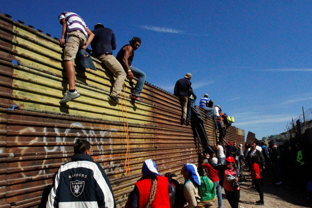 Mỹ bắn hơi cay đuổi người di cư trèo tường vượt biên  - Ảnh 2.