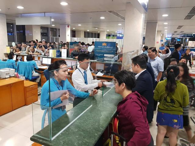 Hành khách trải áo mưa ngủ qua đêm chờ bay ở Tân Sơn Nhất - Ảnh 4.