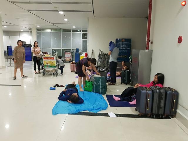 Hành khách trải áo mưa ngủ qua đêm chờ bay ở Tân Sơn Nhất - Ảnh 3.