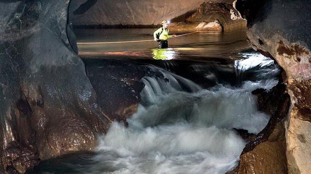 Vượt sông suối, thác nước trong hang Sơn Đoòng - Ảnh: Nguyễn Tâm