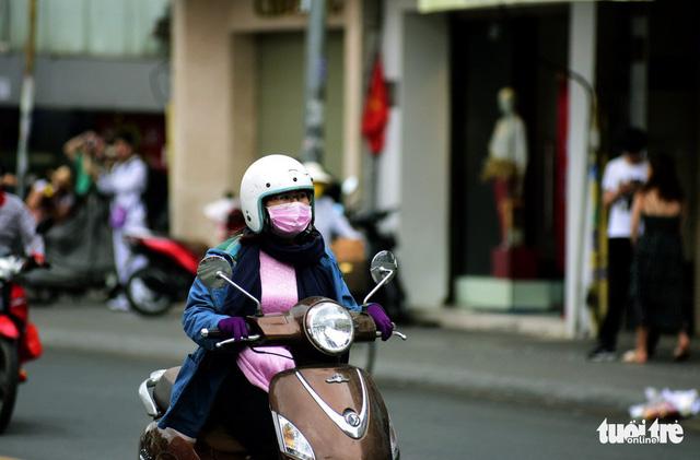 Người Sài Gòn đón năm mới trong se lạnh, mưa rào - Ảnh 1.