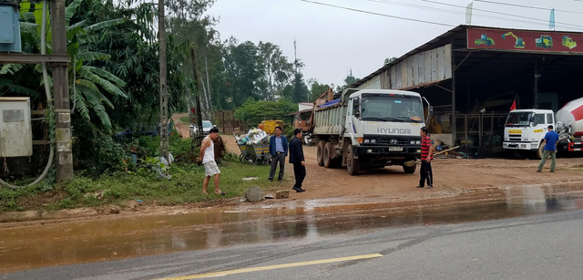 Dân chặn xe tải vì để bùn đất rơi đầy đường - Ảnh 1.