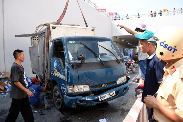 Xe chở nước giải khát lật, người dân giúp tài xế thu gom - Ảnh 1.
