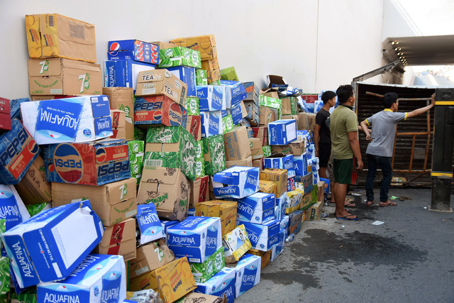 Xe chở nước giải khát lật, người dân giúp tài xế thu gom - Ảnh 2.