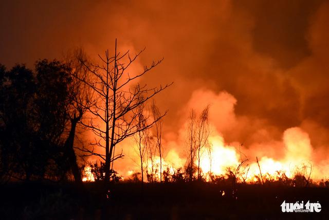 Đồng cỏ cháy rực trời đe dọa hàng chục hộ dân - Ảnh 1.