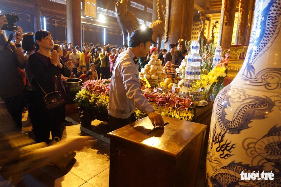Vất vả nhặt tiền lẻ du khách đặt vào ban thờ Phật chùa Bái Đính - Ảnh 13.