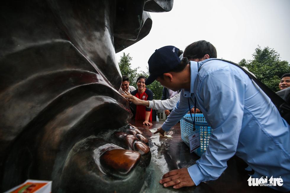 Vất vả nhặt tiền lẻ du khách đặt vào ban thờ Phật chùa Bái Đính - Ảnh 12.