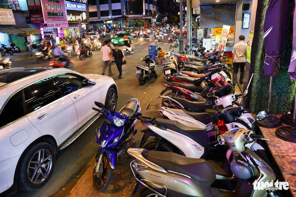 Vỉa hè Sài Gòn lại bị chiếm trọn làm quán nhậu, bãi xe - Ảnh 1.
