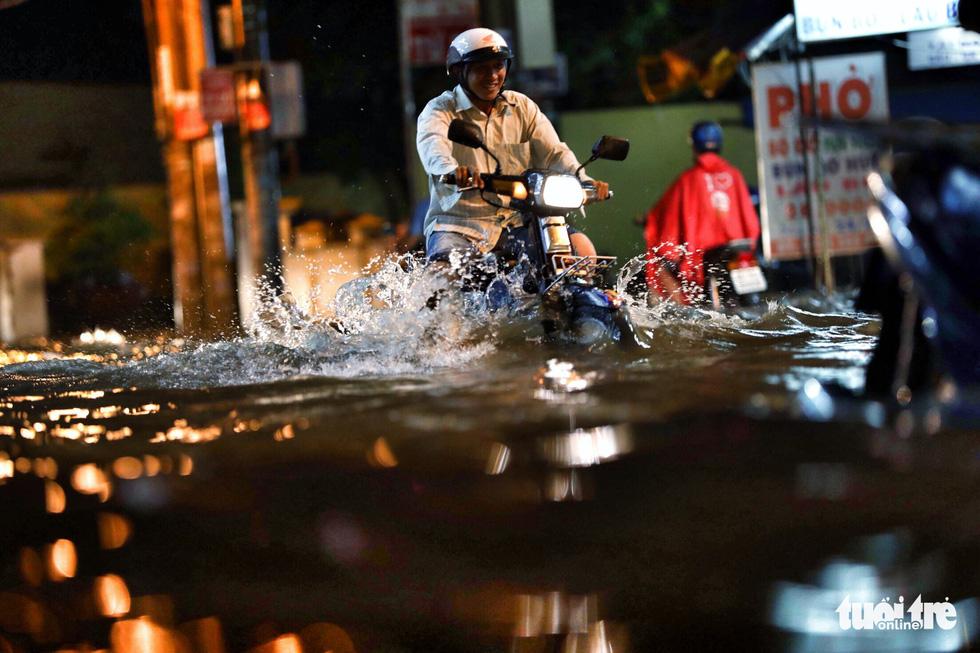 TP.HCM ngập nặng, người dân bì bõm dắt xe về lúc nửa đêm - Ảnh 1.