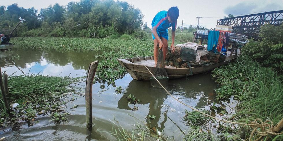 mới 15 tuổi nhưng cậu bé này đã hơn 10 năm theo cha mẹ đi tìm những luồng cá sông - ảnh quốc việt