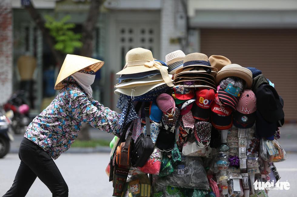 Người Hà Nội kín mít như ninja trong cái nóng gần 40 độ C - Ảnh 1.
