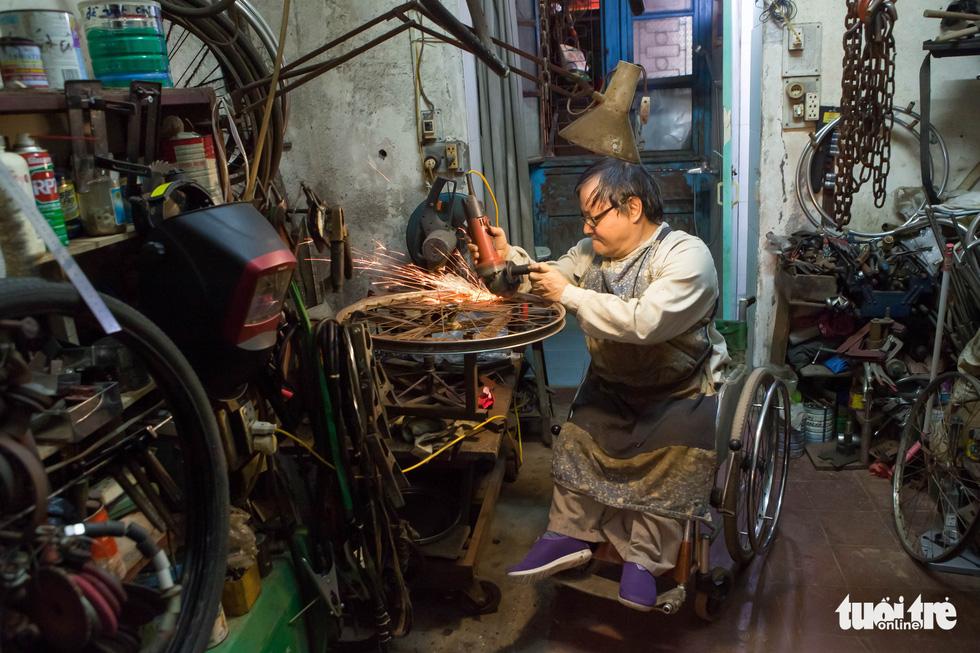 Người đàn ông ngồi xe lăn 20 năm làm xe cho người cùng cảnh ngộ - Ảnh 1.