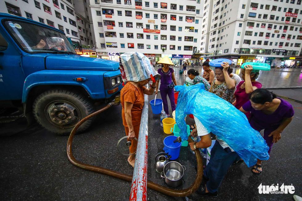 Người dân Hà Nội đội mưa hứng nước sạch - Ảnh 2.