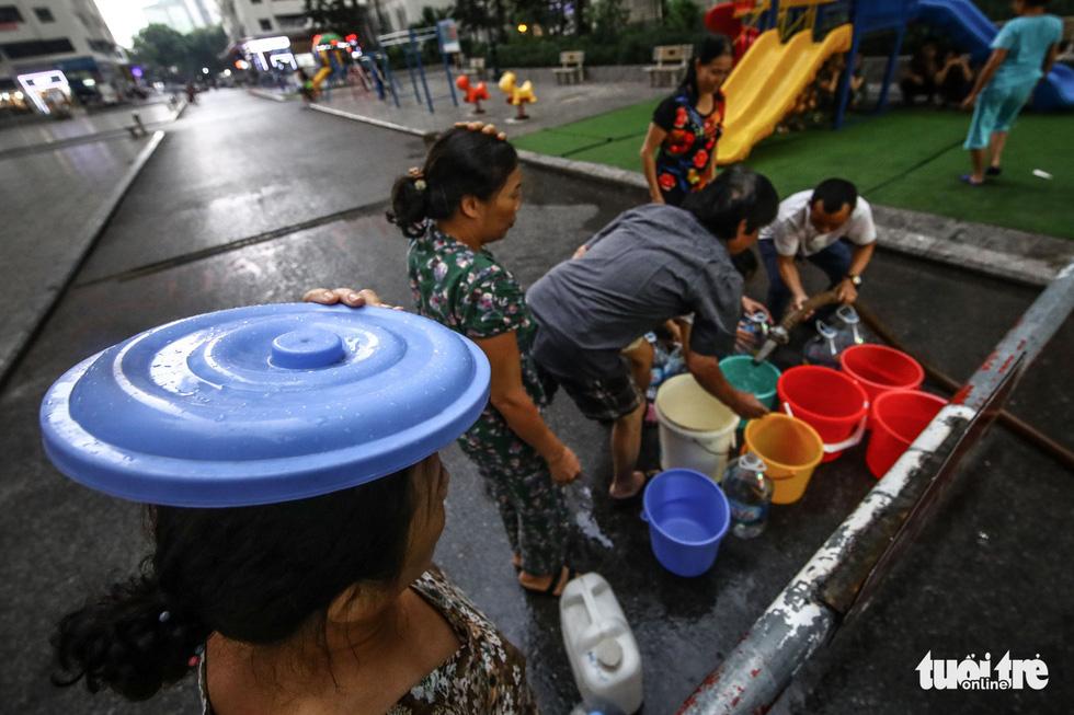 Người dân Hà Nội đội mưa hứng nước sạch - Ảnh 3.