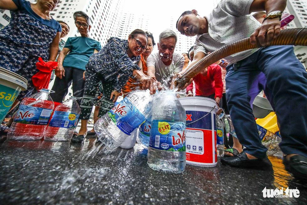 Người dân Hà Nội đội mưa hứng nước sạch - Ảnh 6.