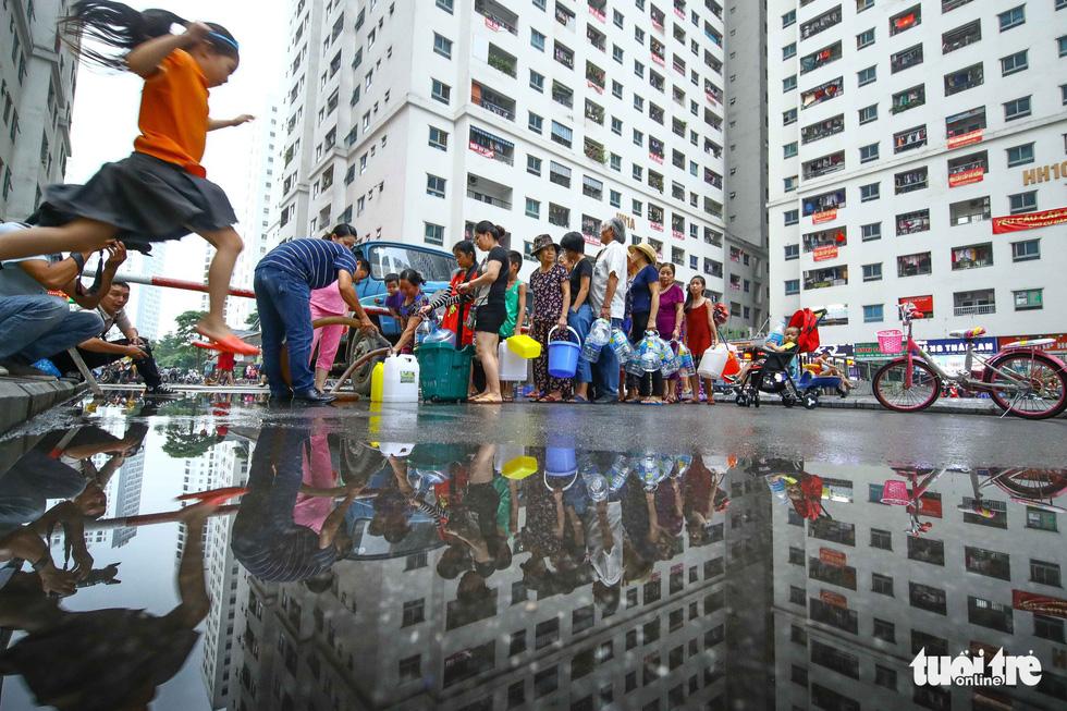 Người dân Hà Nội đội mưa hứng nước sạch - Ảnh 7.